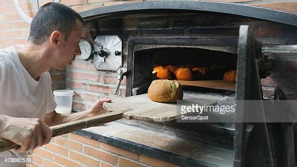Baker checking a bread loaf in a traditional stove.