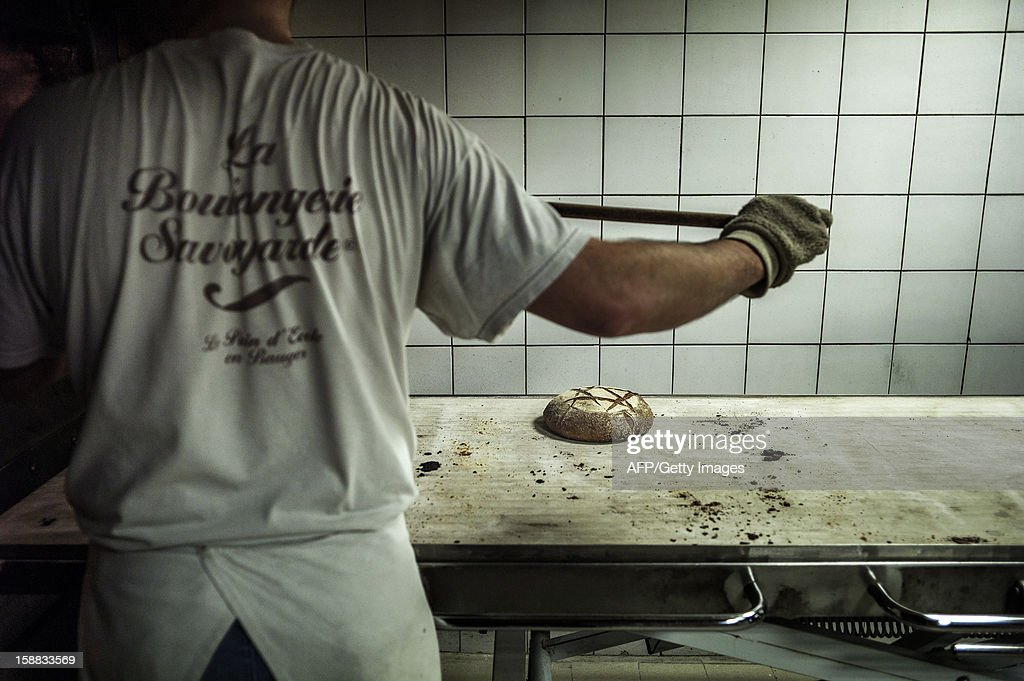 A baker controls bread after its baking, on December 27, 2012 in a bakery of Ecole en Bauges, French Alps.