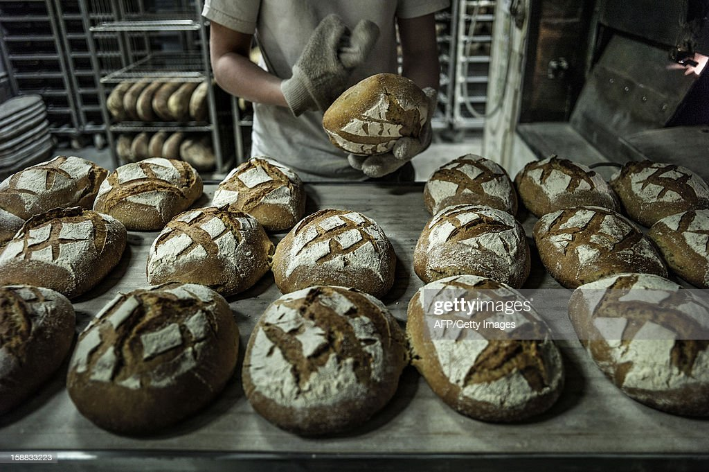 A baker controls breads after baking, on December 27, 2012 in a bakery of Ecole en Bauges, French Alps.