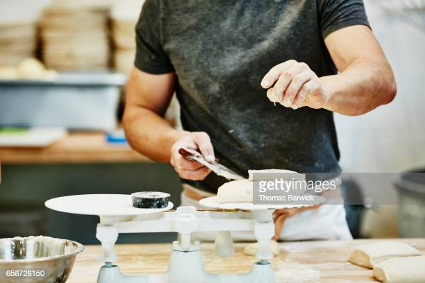 Baker cutting and weighing dough in bakery