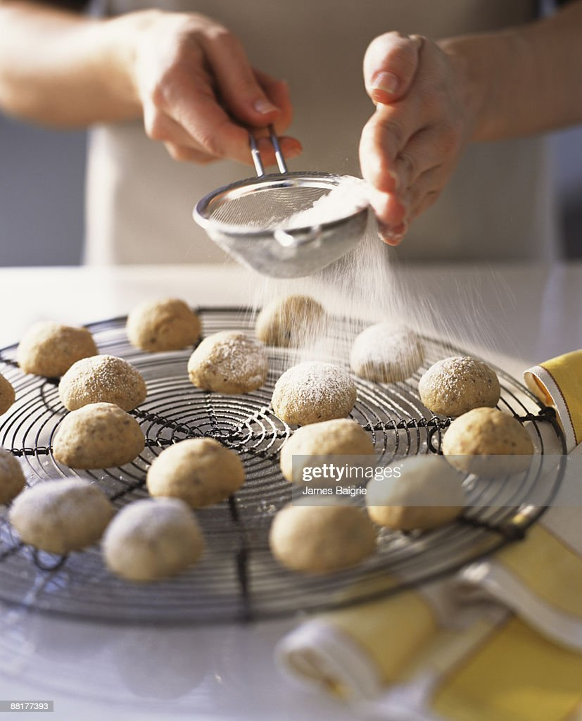 Baker dusting cookies with powdered sugar : Stock Photo