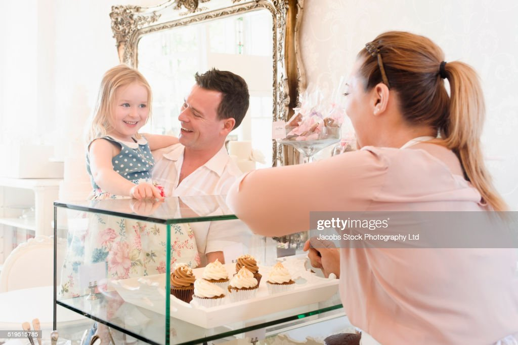 Baker helping father and daughter choose pastries in bakery
