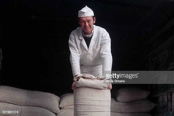 Baker Holding a Sack of Flour
