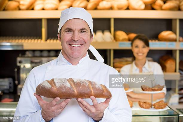 Baker holding bread at a bakery