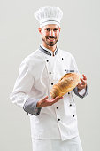 Baker is  holding  bread on gray background.