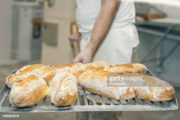 Baker holding cooked bread using shovel