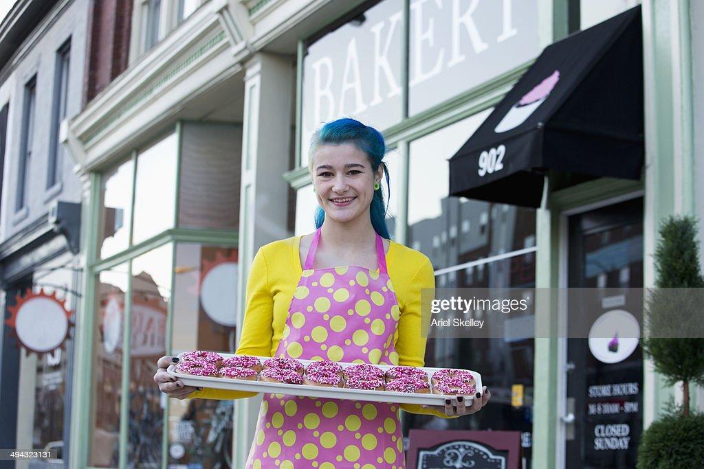 Baker holding donuts outside shop : Stock Photo