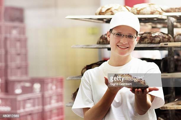 Baker holding fresh bread