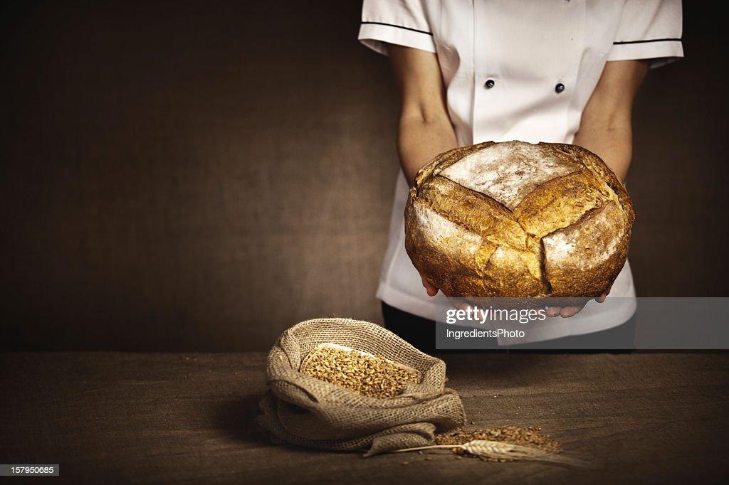 Baker holding in hands fresh baked bread. : Stock Photo