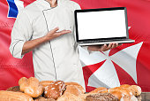 Baker holding laptop on Wallis And Futuna flag and breads background. Chef wearing uniform pointing blank screen for copy space.