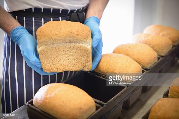 Baker holding loaf of freshly baked bread