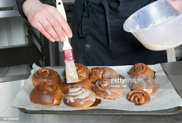 A baker icing buns on a tray.