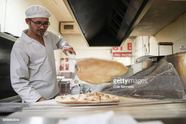 A baker in an Afghan bakery in the southwestern suburb of Lakemba pulls bread out of a claypot oven on May 27 2017 in Sydney Australia Muslims around...