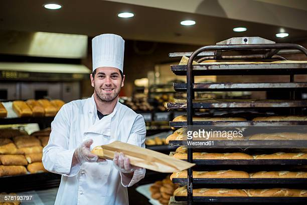 Baker in supermarket packing fresh braed