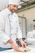 Baker in white chefs uniform kneading dough on bakehouse table