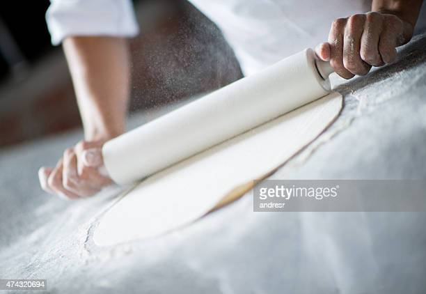 Baker kneading dough with a rolling pin