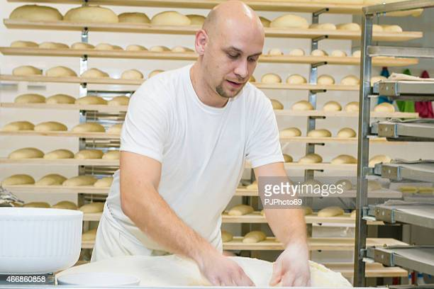 Baker kneading leavened dough on working table