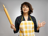 Baker lady with a wooden rolling pin over gray background