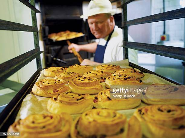 Baker Lifting a Tray of Danish Pastries From a Trolley, Food Processing, Grimsby, UK