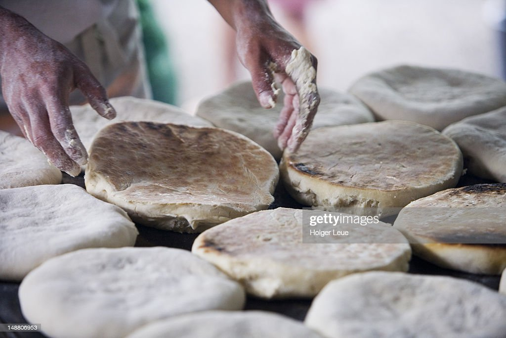 Baker makes Bolo de Caco leavened flatbread at Sunday market. : Stock Photo