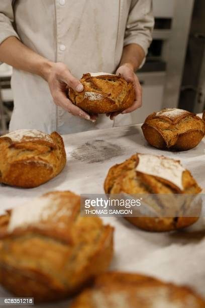 A baker makes bread in the bakery of an hypermarket store of French retail giant Carrefour in Villeneuvelagarenne near Paris on December 7 2016 / AFP...
