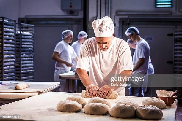Baker making bread, kneading dough