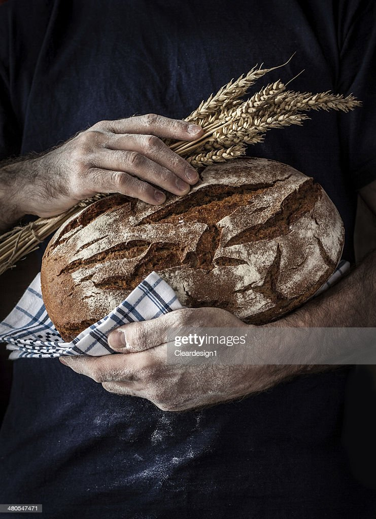 Baker man holding loaf of bread and wheat in hands : Stock Photo