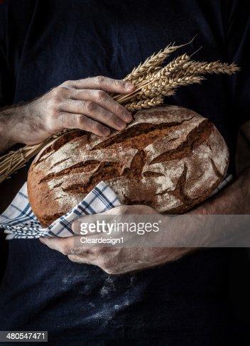 Baker homem a segurar carcaça e trigo nas Mãos : Foto de stock