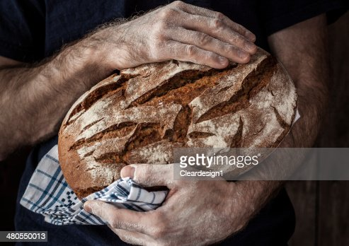 Baker man holding rustic loaf of bread in hands : Stock Photo