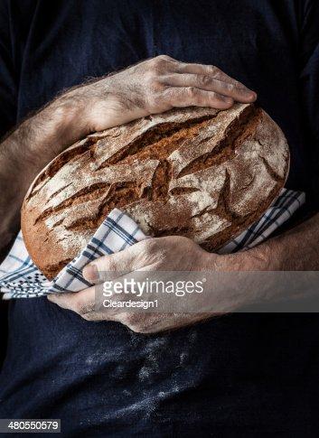 Baker hombre que agarra rústico trozo de pan en las manos : Foto de stock