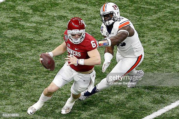 Baker Mayfield of the Oklahoma Sooners avoids a tackle by Carl Lawson of the Auburn Tigers during the Allstate Sugar Bowl at the MercedesBenz...