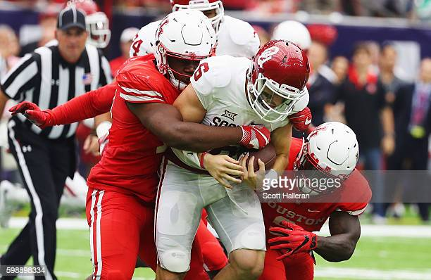 Baker Mayfield of the Oklahoma Sooners is tackled by a group of Houston Cougars in the first half of their game during the Advocare Texas Kickoff on...