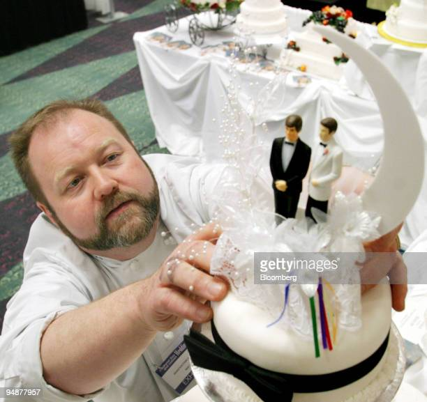Baker Michel Danis of Montreal adjusts a pair of same sex cake toppers at the first National Gay and Lesbian Wedding Show in Toronto Ontario Canada...