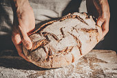 Baker or cooking chef holding fresh baked bread and putting it on table. Closeup. Horizontal.