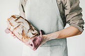 Baker of cooking chef holding fresh baked bread in hands. Concept of cooking, successful businessman or start up. Horizontal.
