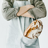 Baker of cooking chef holding fresh baked bread in hands. Concept of cooking, successful businessman or start up. Horizontal with copy space.