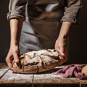 Baker of cooking chef putting fresh baked bread on table. Concept of cooking, successful businessman or start up. Closeup. Horizontal.