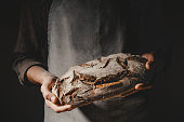 Baker or cooking chef holding fresh baked bread on dark grey background Closeup. Horizontal.