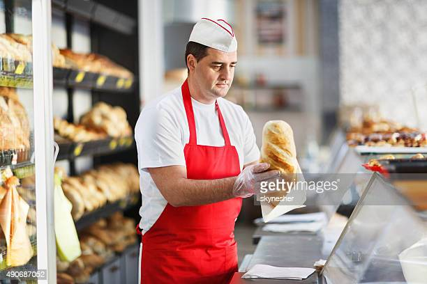 Baker packing loaf of bread in bakery.