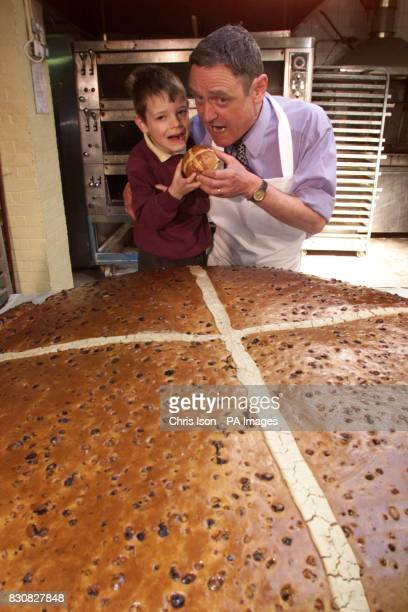 Baker Paul Pegrum and his son Vincent five prepare to tuck into a huge hot cross bun at Pegrum's Bakery in Rustington East Sussex which has been...