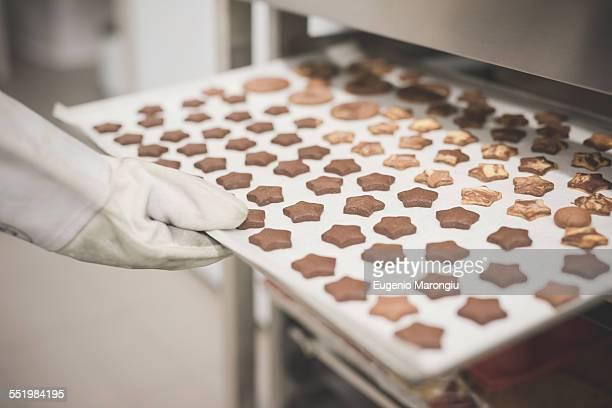 Baker placing tray of star-shaped cookies into oven