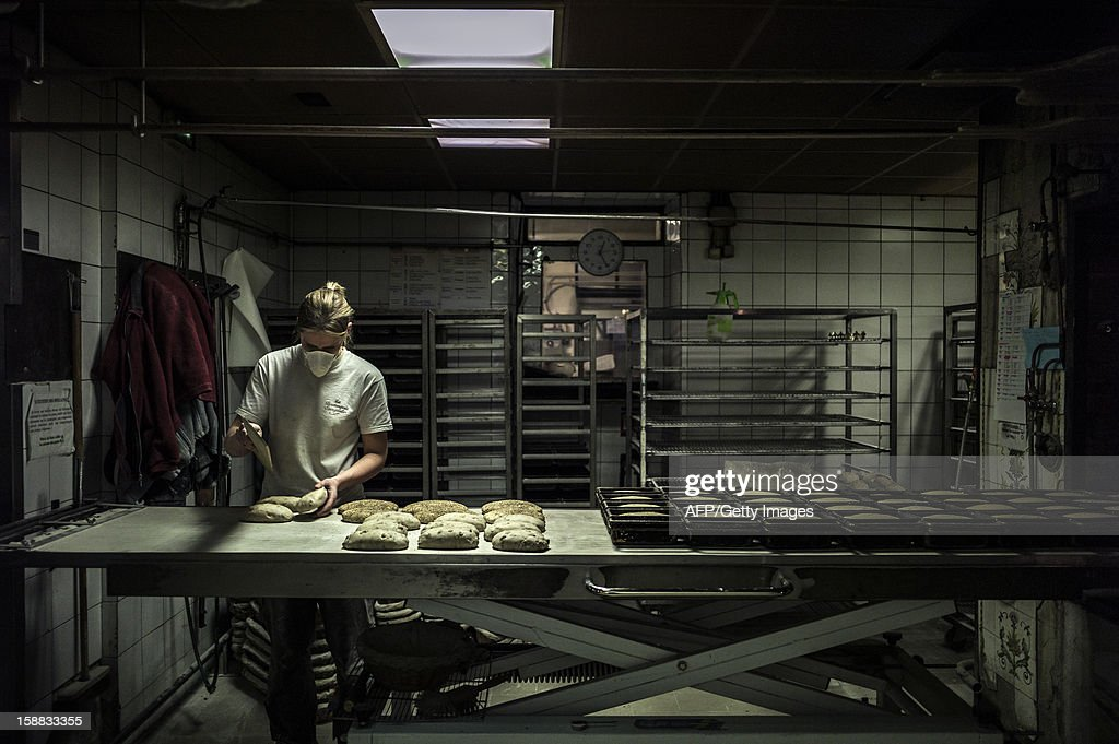 A baker prepares bread for baking, on December 27, 2012 in a bakery of Ecole en Bauges, French Alps.