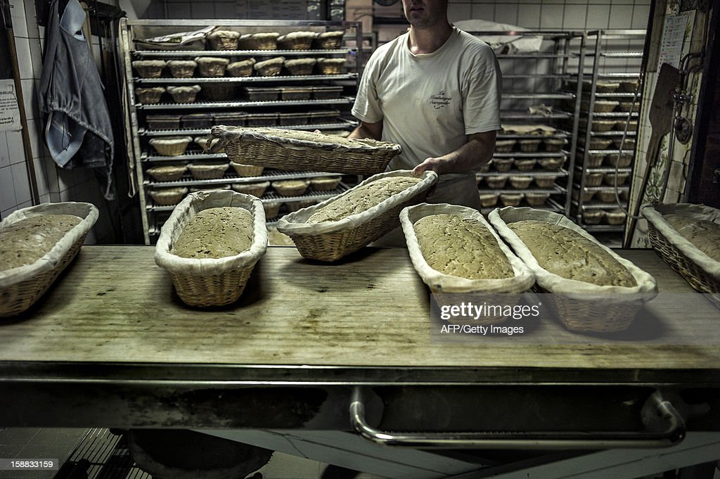 A baker prepares breads for baking, on December 27, 2012 in a bakery of Ecole en Bauges, French Alps.