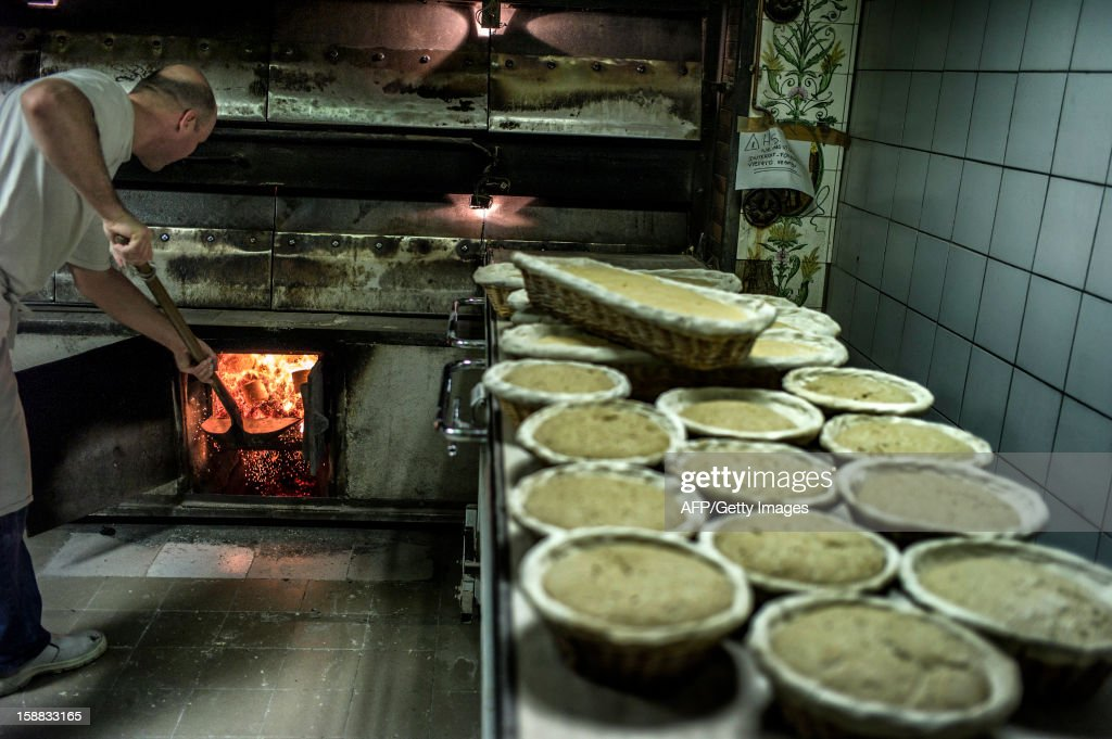 Baker prepares the bread oven before baking bread, on December 27, 2012 in a bakery of Ecole en Bauges, French Alps. AFP PHOTO / JEFF PACHOUD