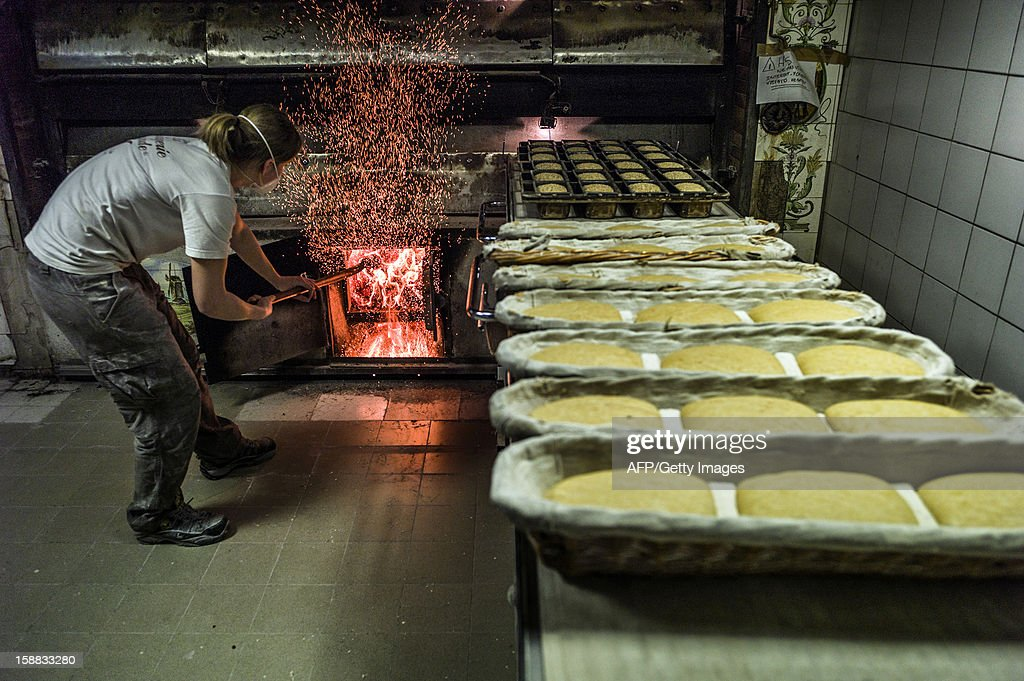 A baker prepares the bread oven before baking the bread, on December 27, 2012 in a bakery of Ecole en Bauges, French Alps.