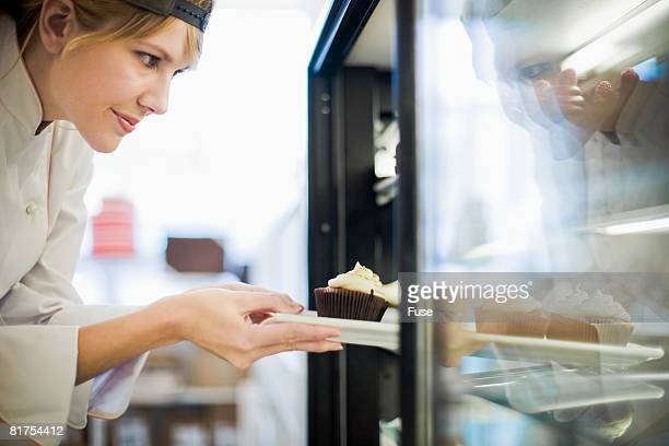 Baker Putting Dessert in Display Case