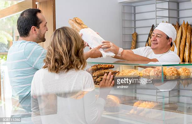 Baker serving a couple of customers at the bakery