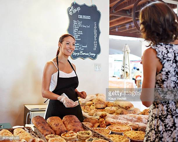 Baker shop owner serving customer at food market