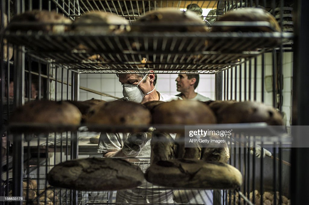 A baker stores baked breads, on December 27, 2012 in a bakery of Ecole en Bauges, French Alps.