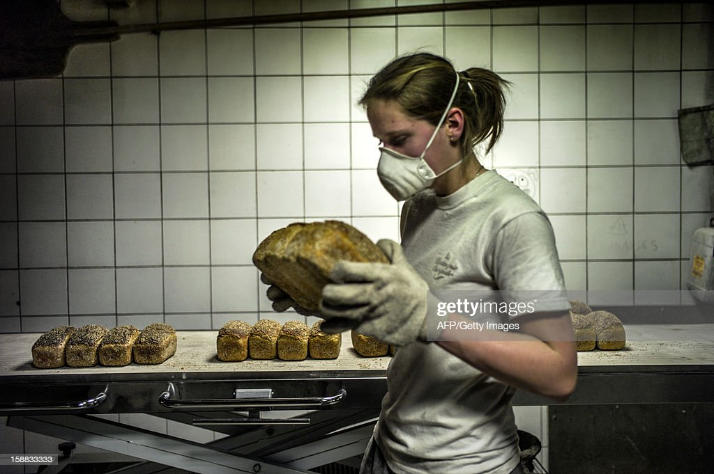 A baker stores bread after its baking, on December 27, 2012 in a bakery of Ecole en Bauges, French Alps.